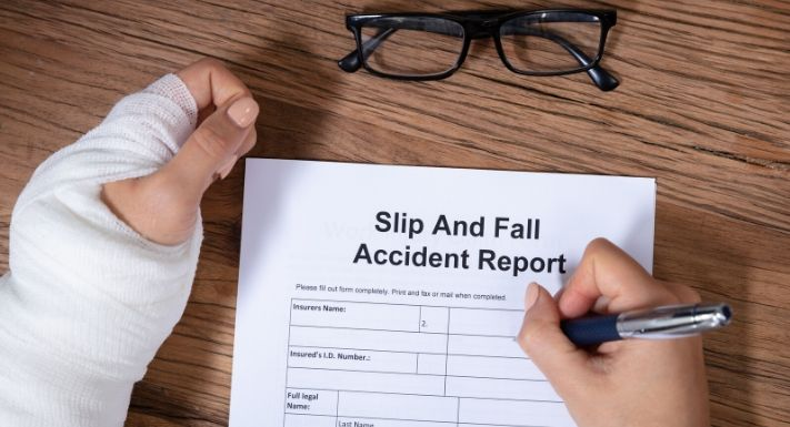 "A person filling out a ""Slip and Fall Accident Report"" in one hand whereas the other hand is wrapped in a cast."